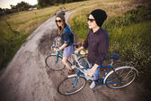Two beautiful hipsters standing outdoor in summer with white vintage fixed gear bicycle — Stock Photo