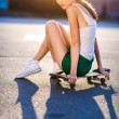 Closeup summer portrait of pretty young woman posing in urban, hipster girl with skate board in town. Summer evening sunlight — Photo #51137081