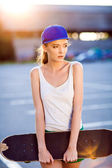 Closeup summer portrait of pretty young woman posing in urban, hipster girl with skate board in town. Summer evening sunlight — Stockfoto