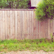 Background rustic wooden fence with green grass, road and tree — Stock Photo