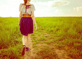 Background girl in a dress and sneakers walking on a footpath in — Foto Stock