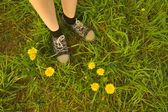 Background feet in sneakers of a girl in the field  — Foto Stock