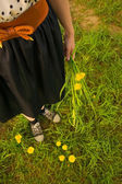 Background girl in a dress and sneakers, holding a dandelion — Stock Photo