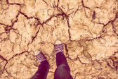 Background feet in sneakers and jeans standing on dry soil — Stock Photo