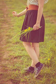Background girl standing in a field in a dress and sneakers  — Stock Photo