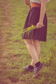 Background girl walking in a field in a dress and sneakers  — Stock Photo