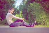 Background girl sitting on the asphalt road among green trees ar — Stock Photo