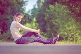 Background girl sitting on the asphalt road among green trees ar — Stock Photo