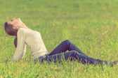 Background girl sitting  on green grass arching her back and eye — Stok fotoğraf