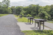 Brown wooden  bench aside the road in day time  — Stock Photo