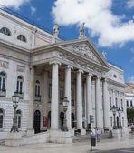 Het gebouw met kolommen en een stucwerk molding op het bovenste gedeelte van een façade van het gebouw tegen de hemel met wolken in Lissabon, portugal — Stockfoto