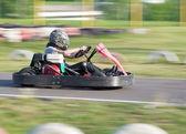 Das kind nimmt an rennen auf ein go-kart im abtransport club — Stockfoto