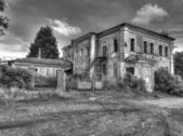 The old uninhabited half-ruined house with broken out — Stock Photo