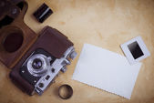 Retro camera with film strip and photo sheet — Stock Photo