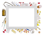 Tablet computer and medical supplies — Stock Photo