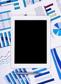 Touchpad above financial paper charts and graphs — Stock Photo