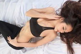 Young beautiful tanned Sexy Asian woman lying in bed — Stock Photo