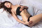 Young beautiful tanned Sexy Asian woman model lying on bed — Stock Photo