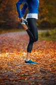 Young woman stretching before running in the early evening in th — Stockfoto