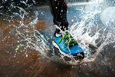 雨の中で実行している単一のランナー — ストック写真