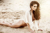 Sexy woman lying in the sand — Stock Photo