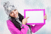 Girl pointing at a blank board — Stock Photo