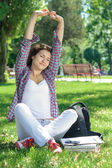 A beautiful woman is sitting on the grass — Stock Photo