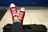 Woman's feet in red sneakers on the suitcase — Stock Photo