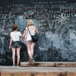 Two young  girls writing on big blackboard — Stock Photo #50678715