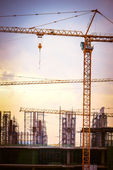 Construction site with cranes on sky, retro tone image — Stockfoto