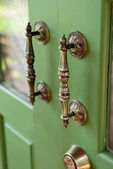 Door handle on green wooden door — Stock Photo