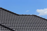 Black tiles roof on a new house with blue sky — Stock Photo