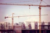 Construction site with cranes, retro tone image — Stock Photo
