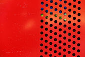 Background of red steel metal with circle perforated holes — Zdjęcie stockowe