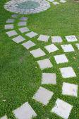 Kamenná cesta cementu v zahradě zelené trávy — Stock fotografie