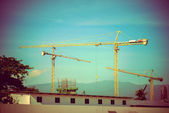 Construction site with cranes on sky background, retro tone — Stock Photo