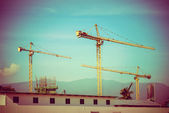 Construction site with cranes on sky background, retro tone imag — Stock Photo