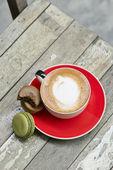 La imagen del café un macarrón de sobre mesa de madera — Foto de Stock