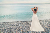 Vintage toned picture of a young bride in a white dress standing on the pebble beach of the azure sea. Nice, France. — Stock Photo