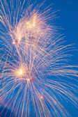Colorful fireworks on the blue cloudy sky background — ストック写真