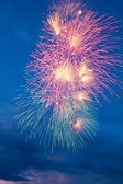 Colorful fireworks on the blue cloudy sky background — Stock Photo