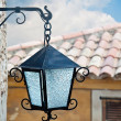 Close up of the street lamp hanging on the wall of an old buildi — Stock Photo