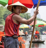 A Chinese man leads a bamboo boat in China — Stock Photo