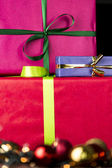 Three wrapped gifts, bowknots, spheres and glitters — Stock Photo