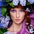 Portrait of a beautiful girl with lilac flower hat lilac — Stock Photo #49595309