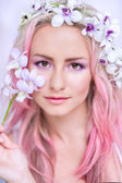 Tender girl with pink hair in these orchids — Stockfoto