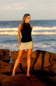 Black Top - Silver Gray Skirt - Ocean Wave and Rock Background — Stock Photo