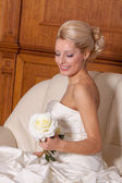 Portrait of beautiful bride with blond hair sitting on a sofa. — Stock Photo