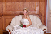Indoor portrait of  beautiful bride with blonde hair sitting on a sofa, holding red roses. — Stock Photo