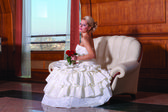 Indoor portrait of adorable bride with blonde hair sitting on a sofa, holding red roses. — Stock Photo